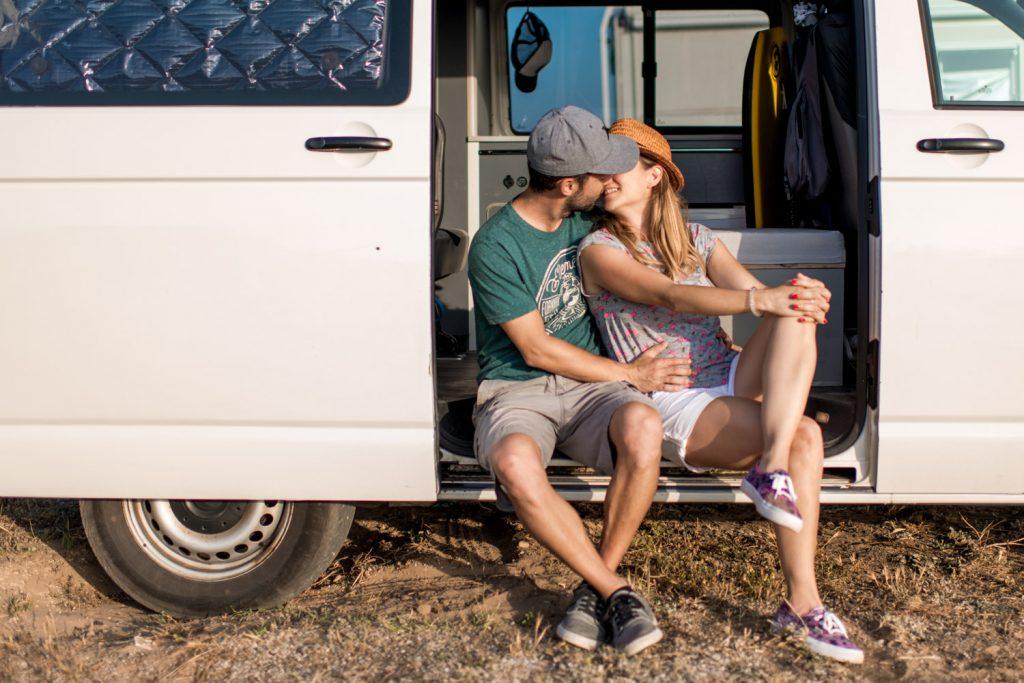 novios besándose en la puerta de su camper